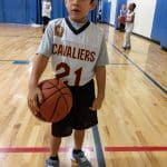 kid holding basketball at YMCA six and under league