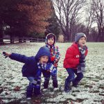 three kids playing in snowy yard after leaving California for Ohio