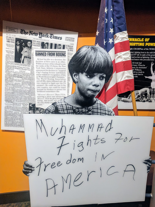 Women holding Muhammad Fights For Freedom In America sign, seen in Muhammad Ali Museum