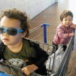 two kids, one wearing sunglasses, in Walmart cart