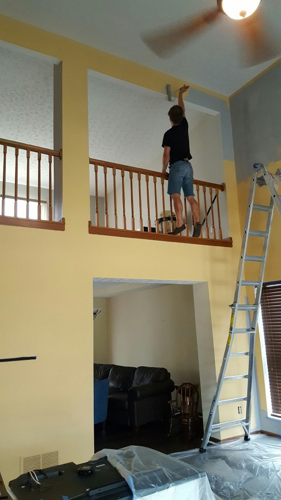 man painting great room with use of tall ladder