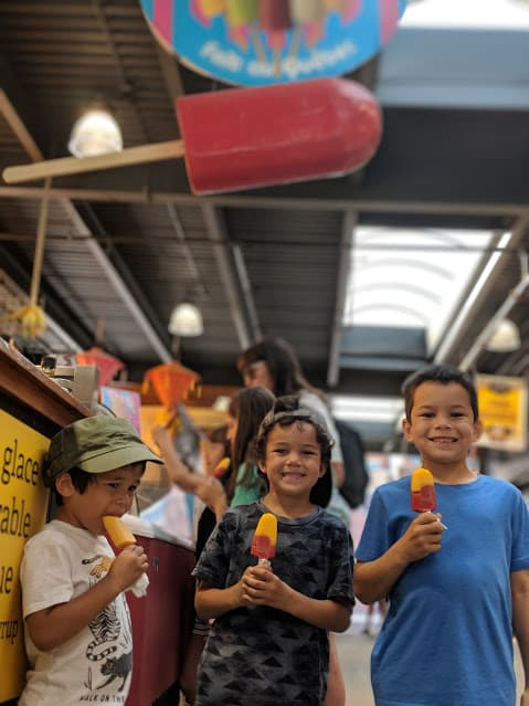 Three kids eating popsicles at Jean-Talon Market in Montreal