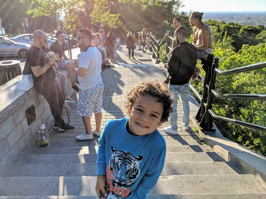 Kid smiling while teens hang out at viewpoint at Parc du Mont-Royal in Montreal