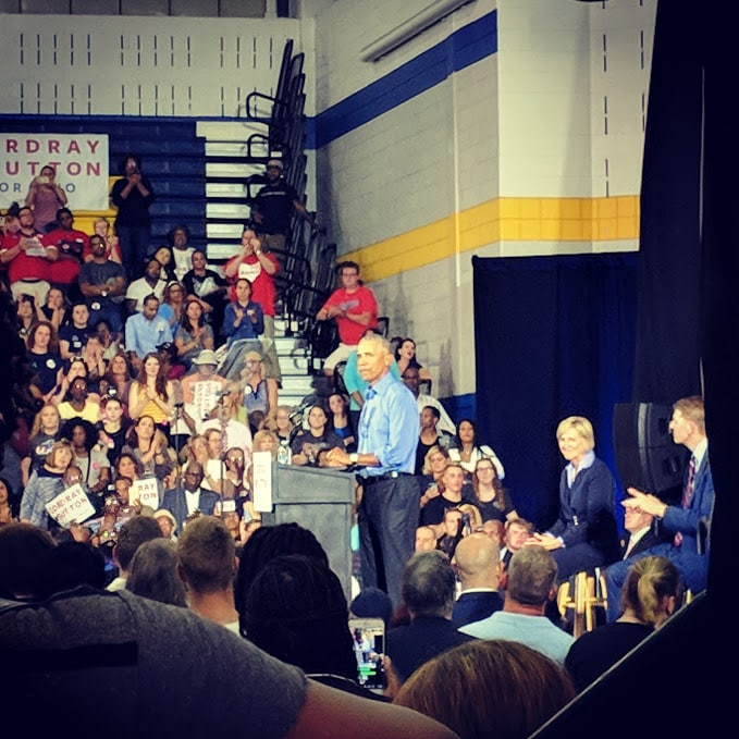 Barack Obama speaking at podium in Cleveland school gymnasium
