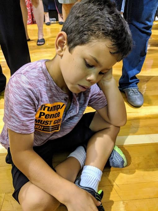 kid sitting on the floor while waiting on President Obama to speak
