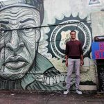Man in front of Harriet Tubman street art mural in New Orleans.