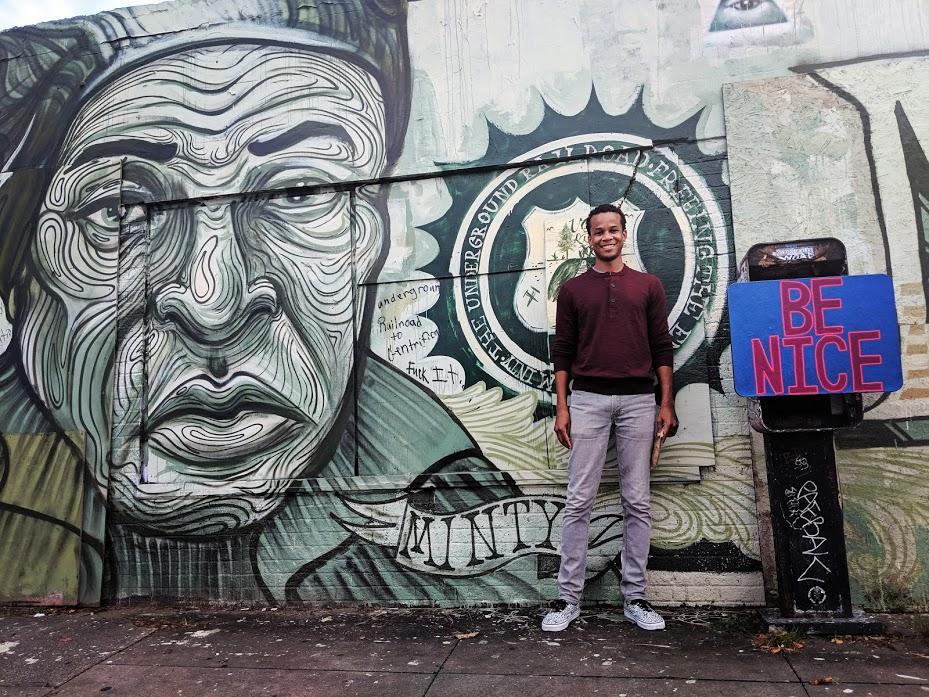 Man in front of Harriet Tubman street art mural in New Orleans.