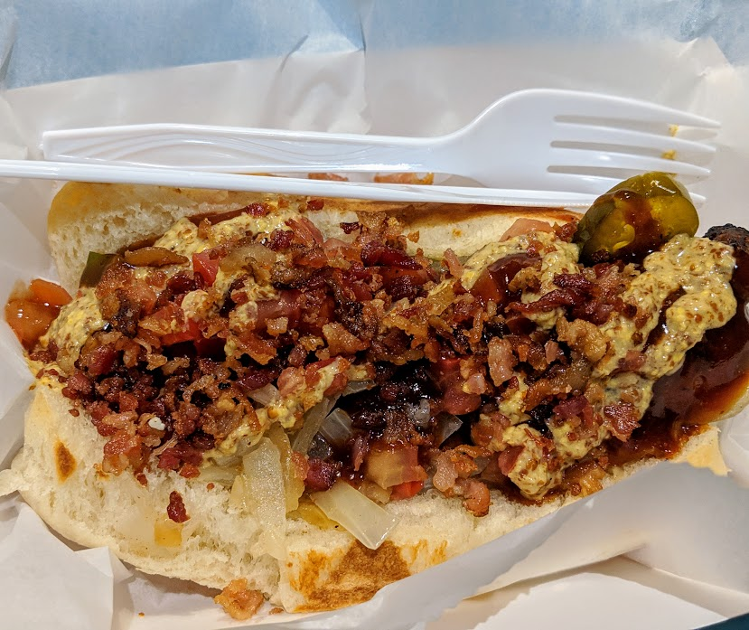 Gator hot dog with bacon, onions, mustard, jalapenos, and tomatoes