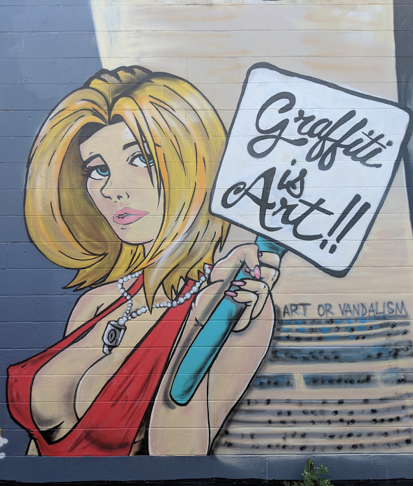 "Blonde woman holding ""graffiti is art"" mural in New Orleans"