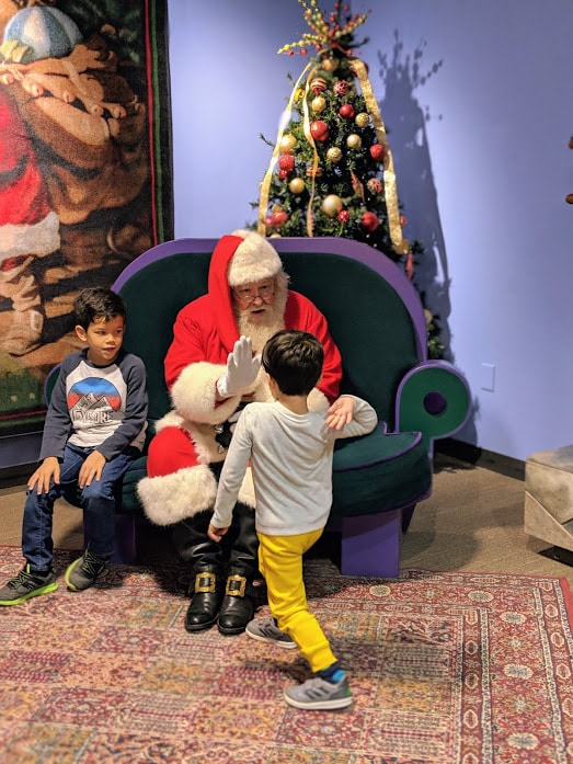 Santa Claus giving kid high-five at Children's Museum of Indianapolis