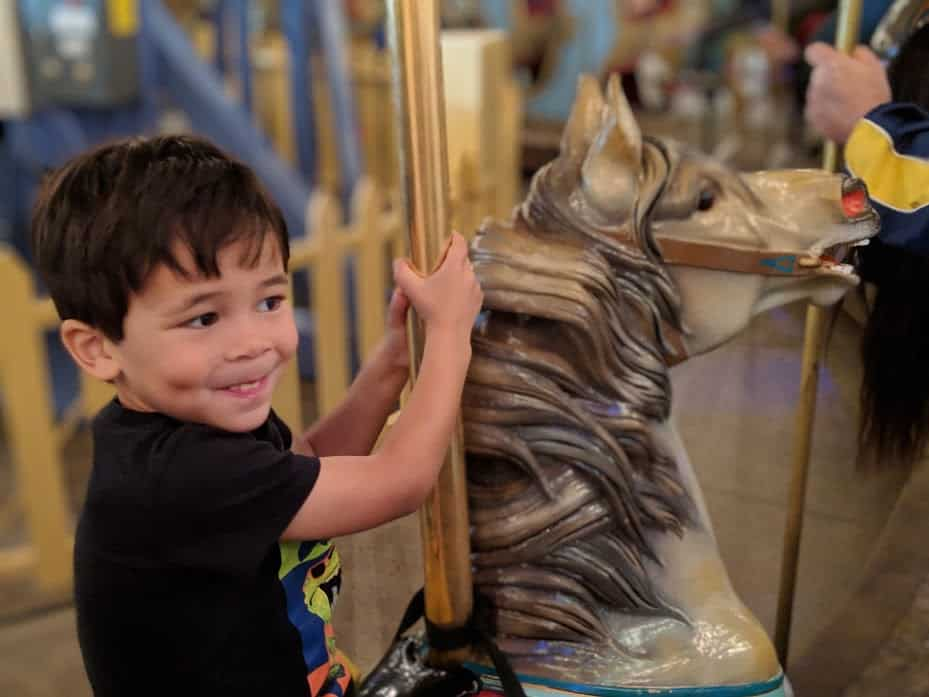 kid riding carousel at Children's Museum of Indianapolis