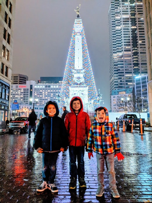 Children posing in rain near Soldiers and Sailors monument in Downtown Indianapolis, Indiana.