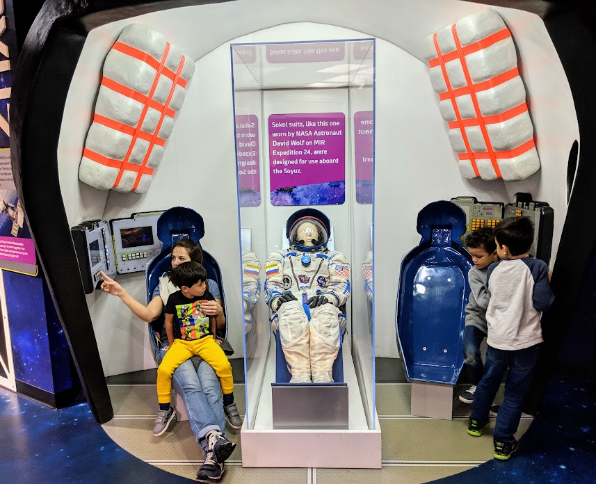 family playing in the space exhibit at the Children's Museum of Indianapolis