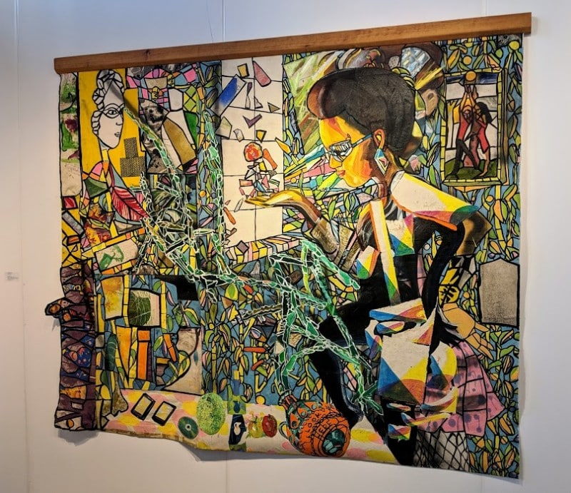 Colorful artwork of woman holding stained glass by Paula Wilson at Prizm Art Fair in Miami.