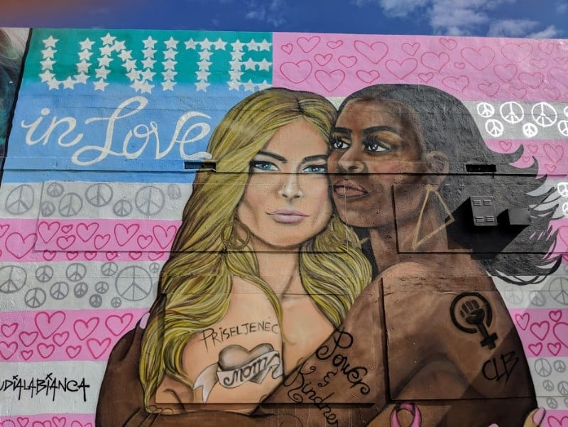 """Unite In Love"" mural of two black and white women holding in each other."