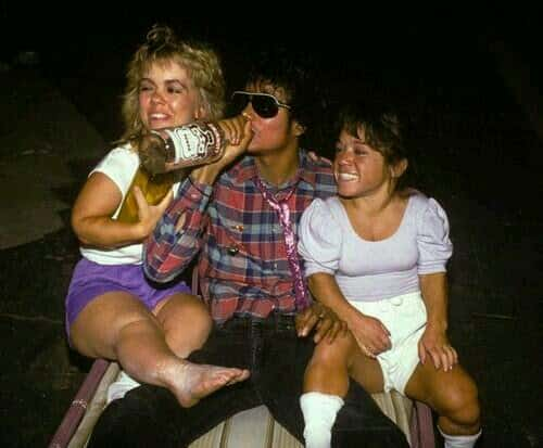 Michael Jackson drinking liquor with two little women sitting on his lap