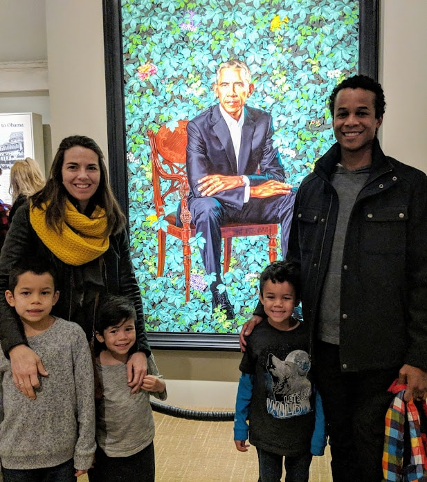 Multiracial family posing in front of Barack Obama portrait at National Portrait Gallery.