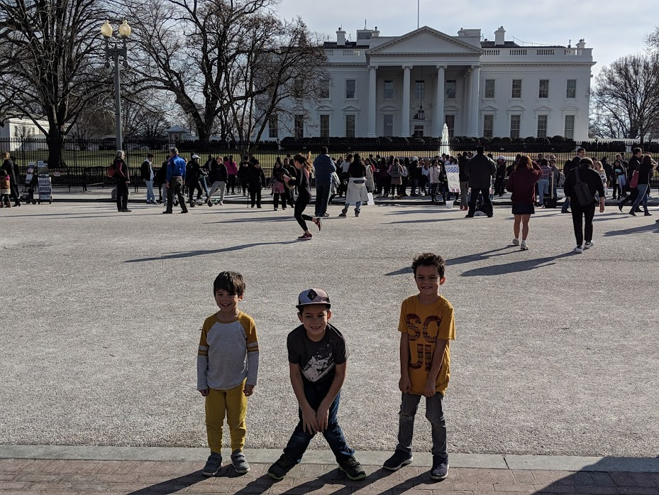 Young kids smiling and posing in front of the White House.