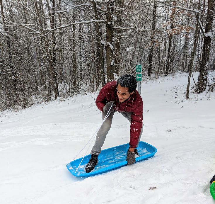 Man standing on sled trying to surf in snow