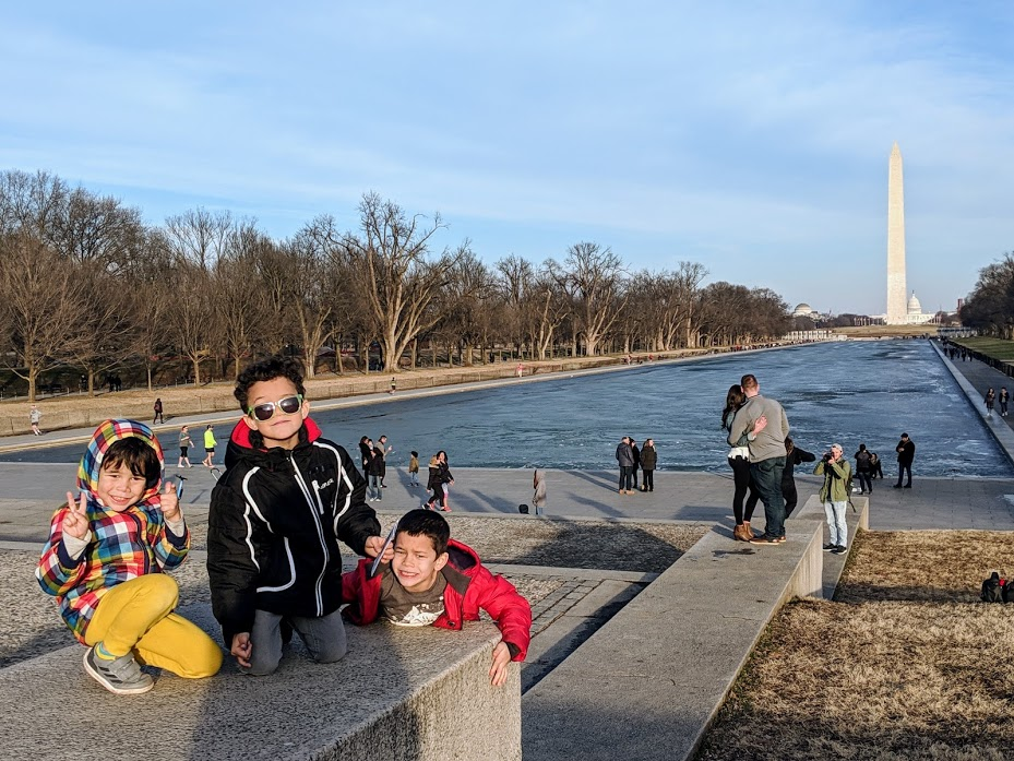 Three kids climbing stairs near Lincoln Memorial in Washington, D.C.