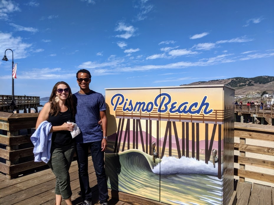 Author and his wife standing in front of a Pismo Beach sign near the pier.