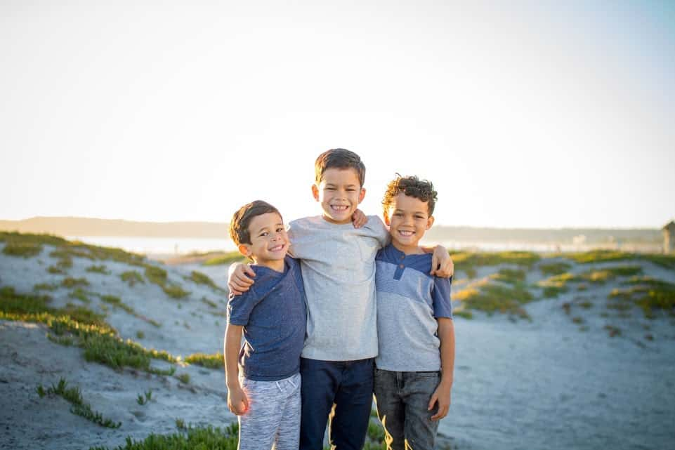 Three biracial boys posing on Coronado Island in San Diego.