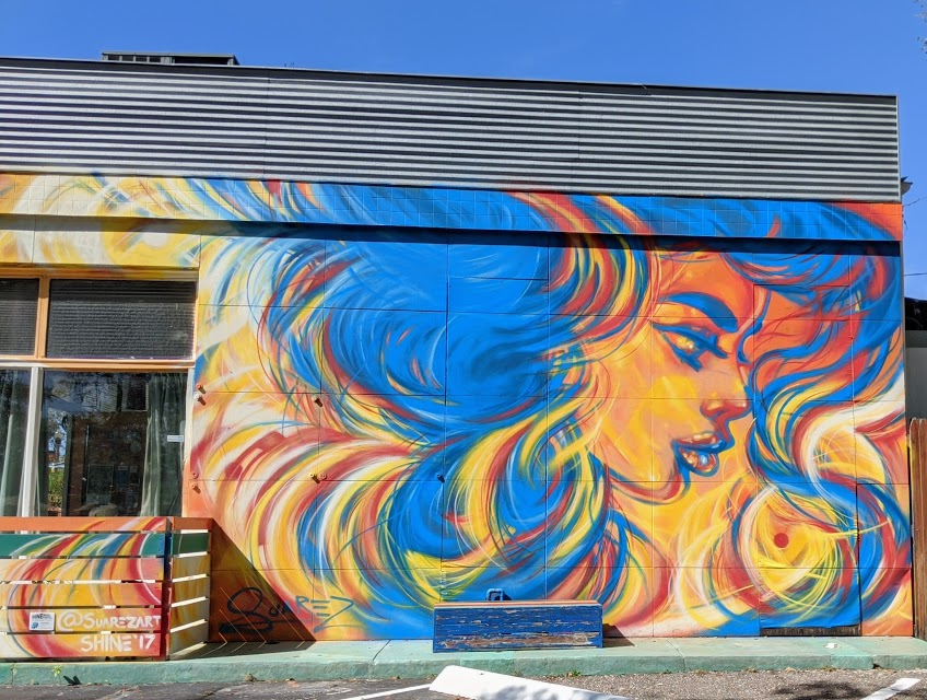Mural of woman with flowing hair on side of cafe in St. Petersburg, Florida.