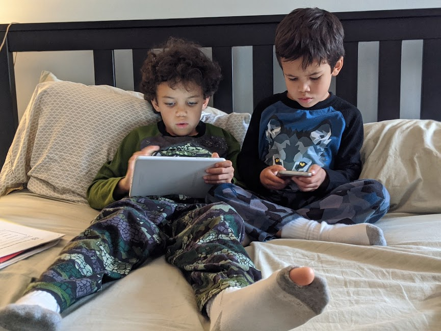 Kids on electronic devices, one has hole in sock